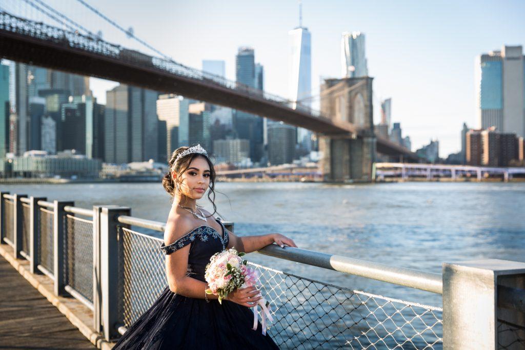 Girl wearing tiara and holding railing with Brooklyn Bridge in background