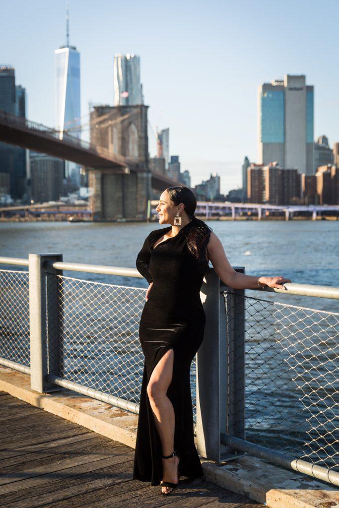 Woman on Brooklyn Bridge Park boardwalk wearing long black dress with split
