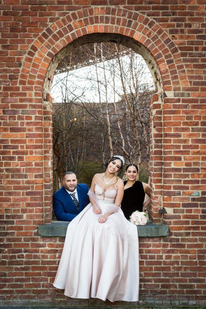 Girl in pink ball gown posing with parents under brick arch