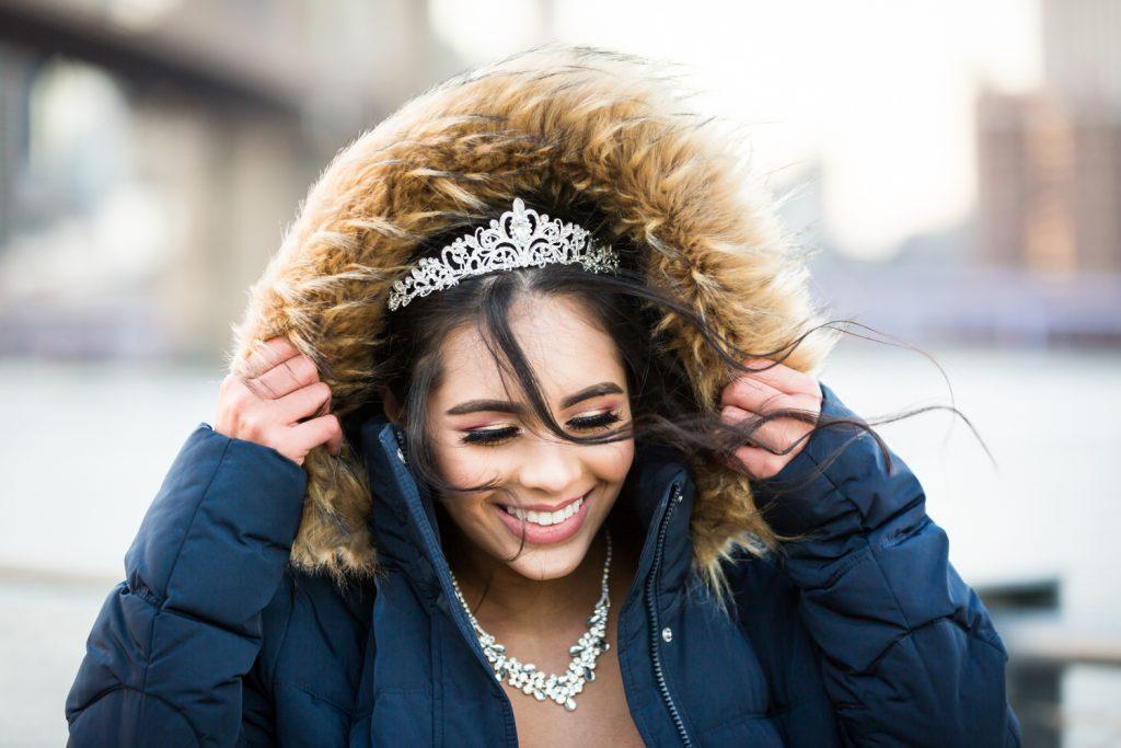Girl holding fur hood of jacket and wearing tiara