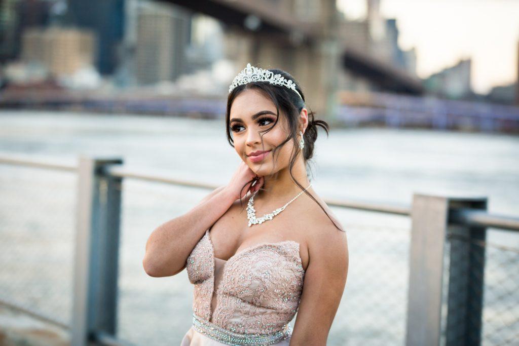 Girl wearing tiara and pink strapless gown on Brooklyn Bridge Park boardwalk